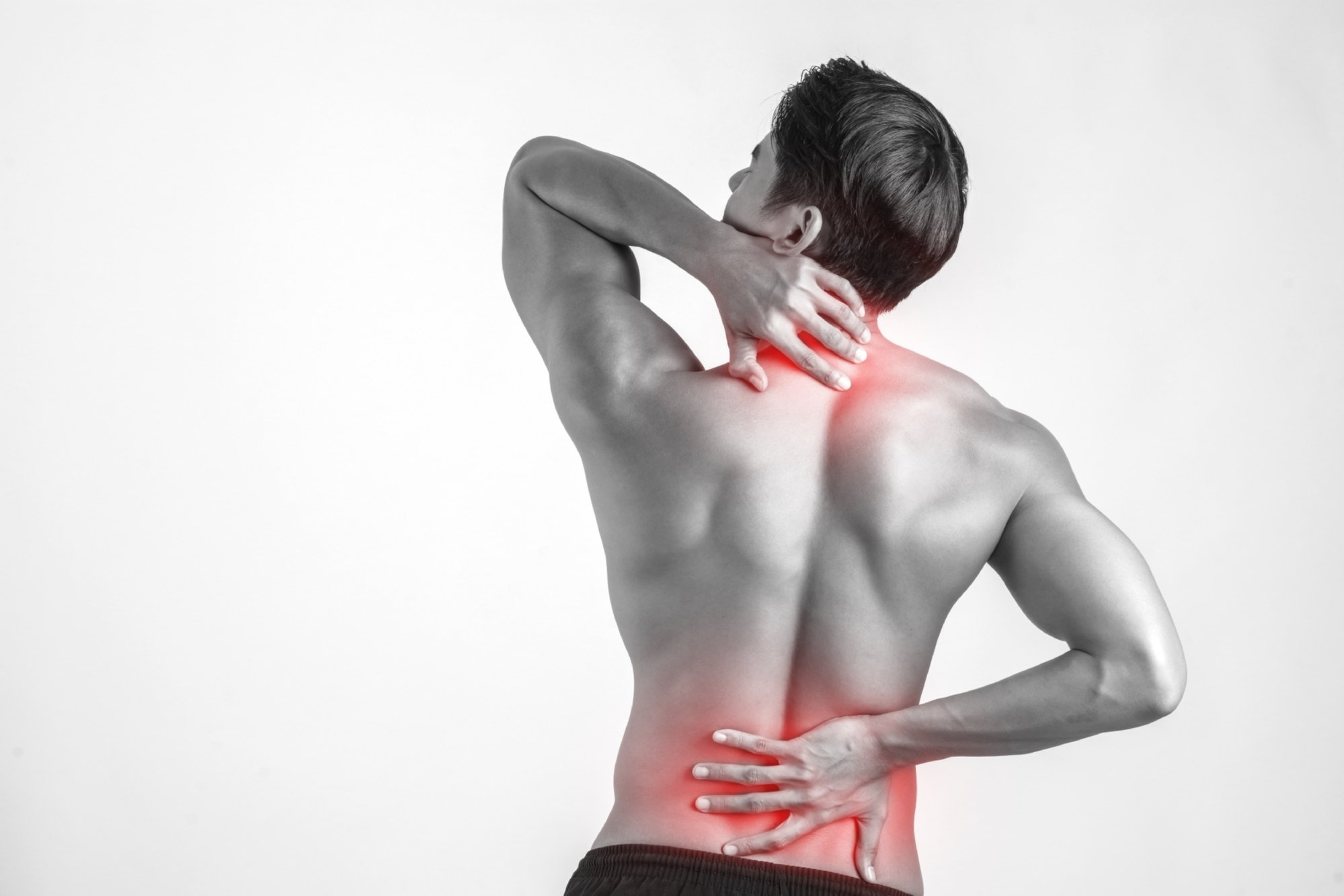 man rubbing his painful back because of back pain